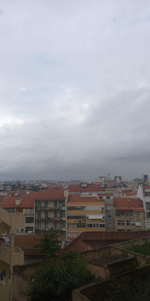 Imagem de um dia cinzento em Lisboa. Grande céu cinzento com a cidade em tons pastel.